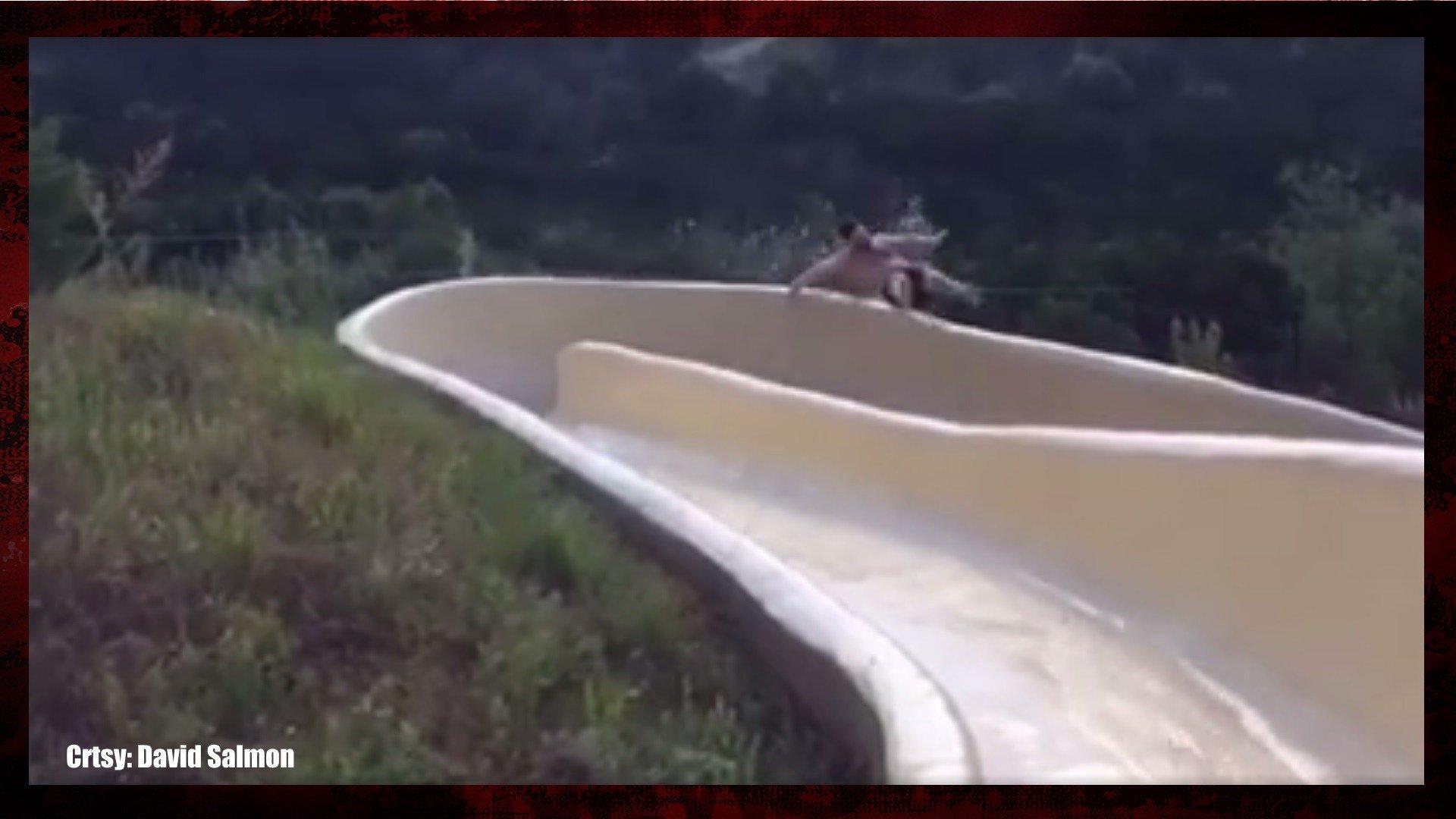Man flies off water slide down rocky cliff