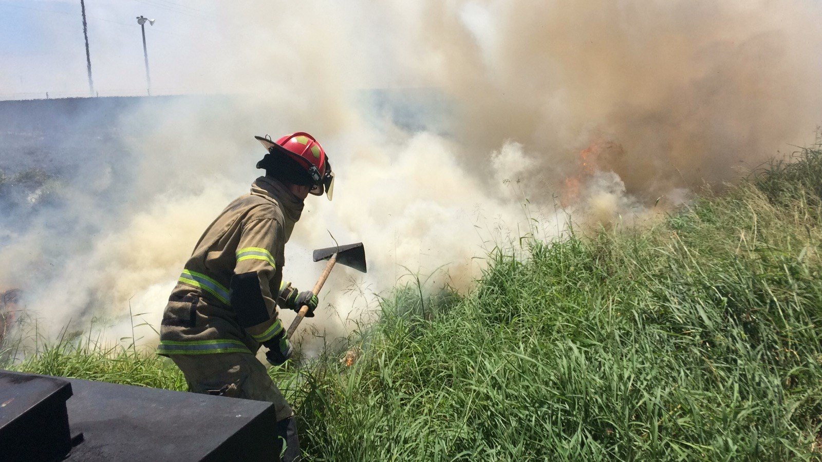 A firefighter tries to put out a brush fire.