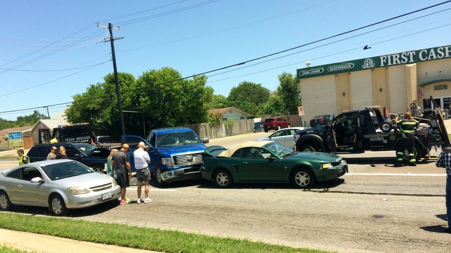 People involved in a four car crash watch wreckers remove the vehicles from the road.