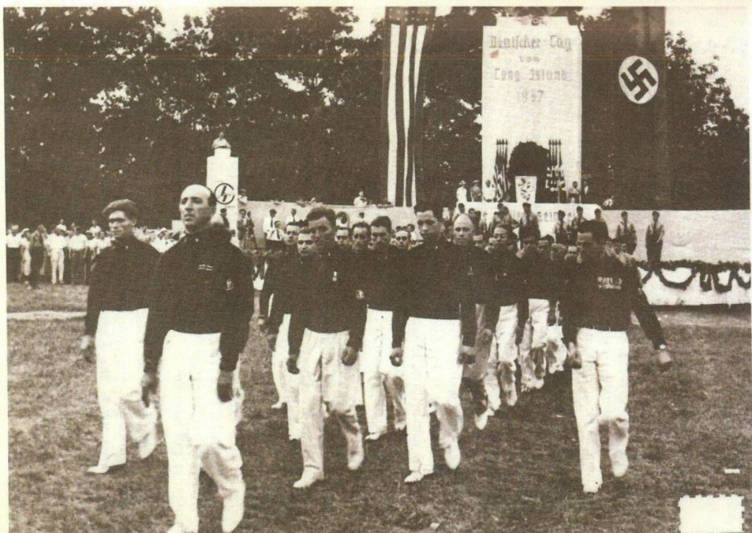 Included in a lawsuit against the German-American Settlement League, this archival photo shows men in Italian Blackshirts uniforms marching under a Nazi flag in Long Island. (Court filing/U.S. District Court, Eastern District of New York)