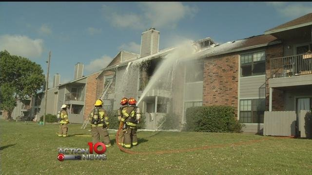 Firefighters spray water and foam on fire at Waters Edge Apartments