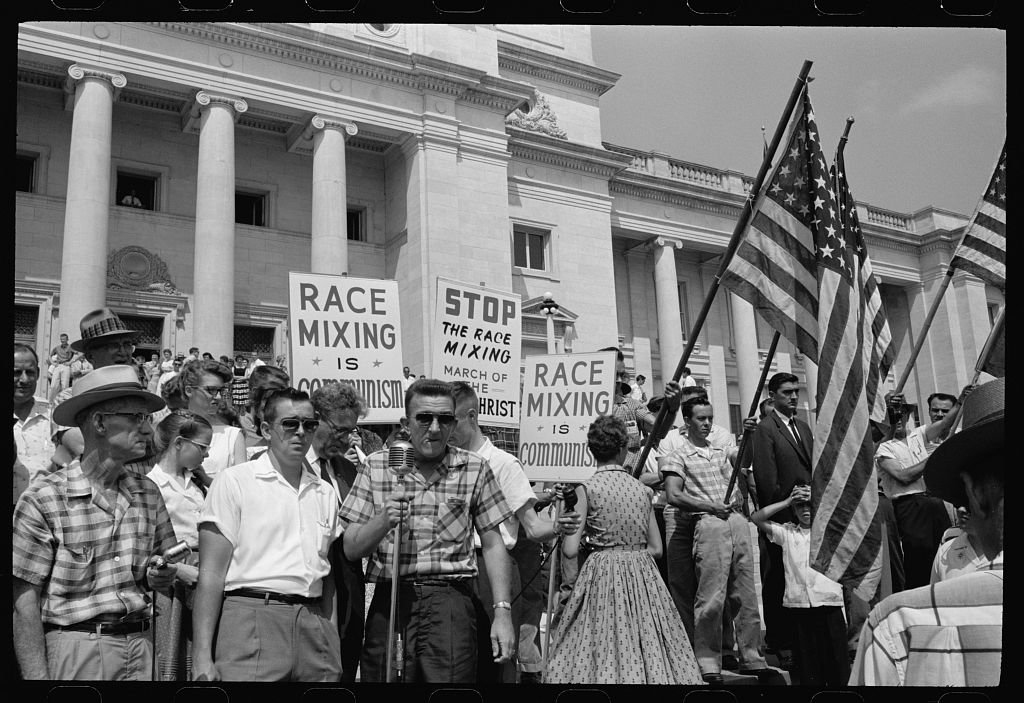 """Photograph showing a group of people, several holding signs and American flags, protesting the admission of the """"Little Rock Nine"""" to Central High School. PHOTO: Library of Congress"""