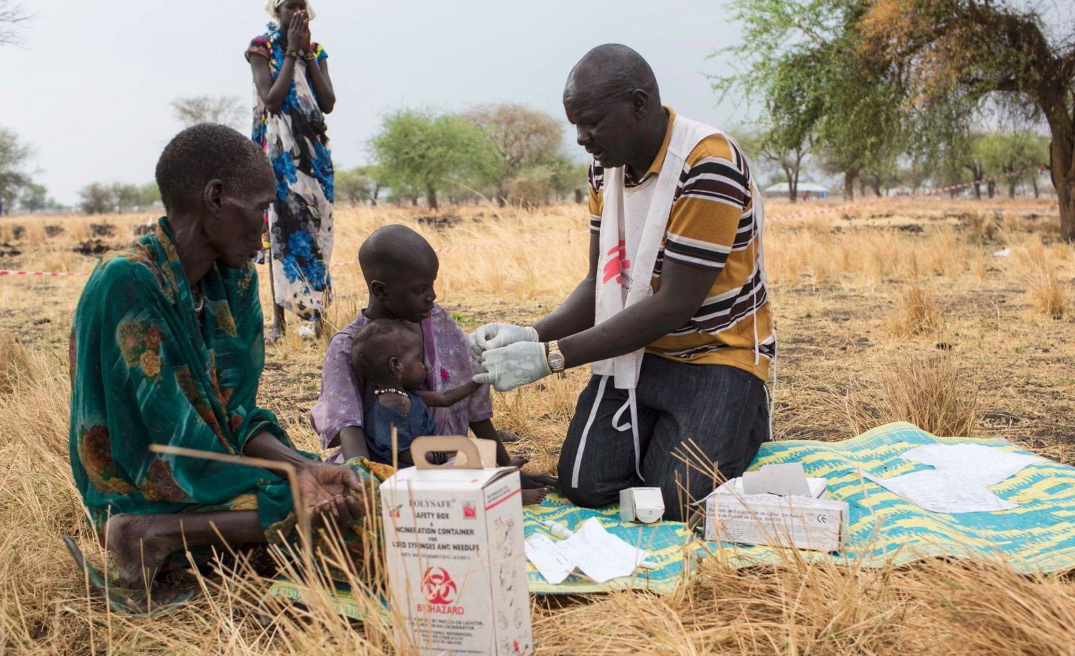 LEER, SOUTH SUDAN – SIEGFRIED MODOLA March 2017 – Community Health Promoter, Gatbel, tests a child for malaria at an outdoor support clinic in Thaker, Leer County, South Sudan. Photo courtesy of Doctors Without Borders.