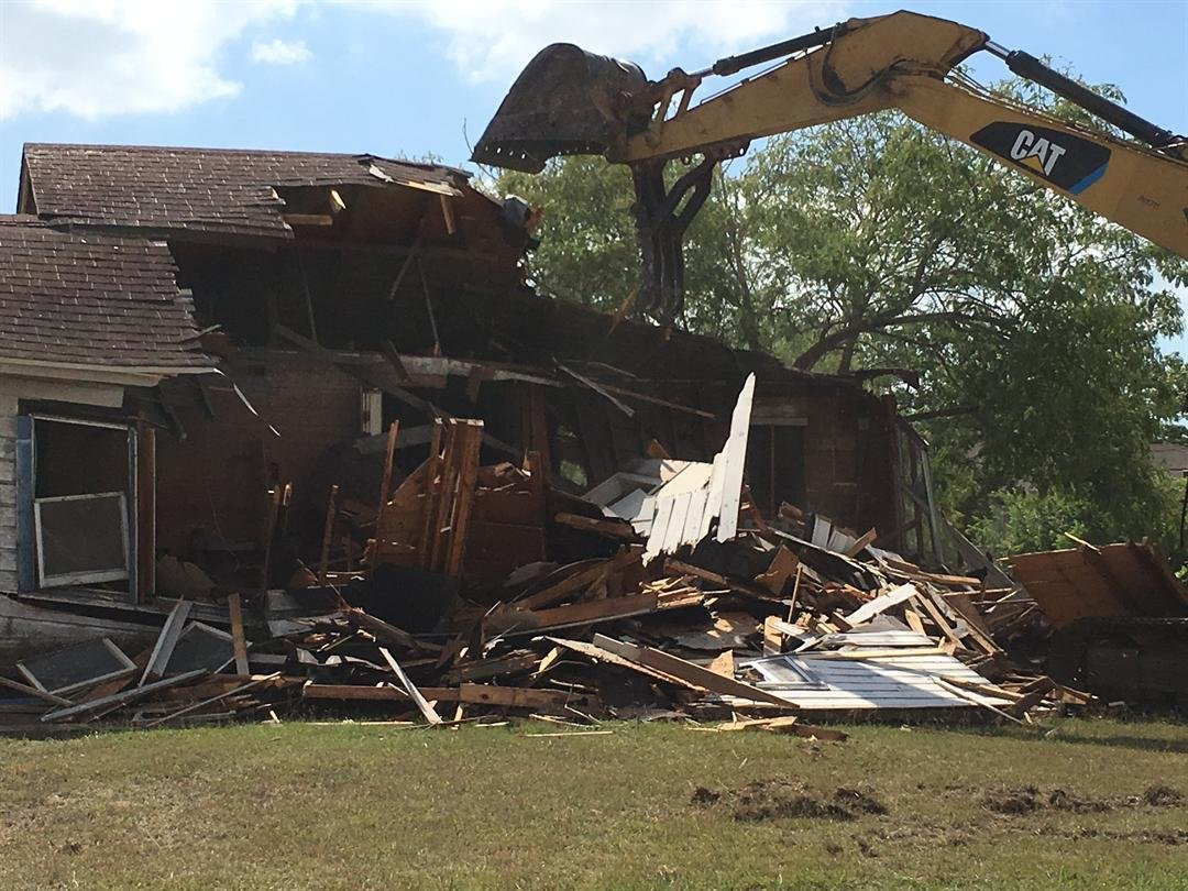 An abandoned house just a few feet away from Shaw Elementary is torn down.